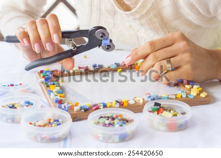 Woman decorating photo frame with colorful glass mosaic - stock photo