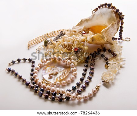 woman decorations in a shell on a white background .beads, rings, pearls.