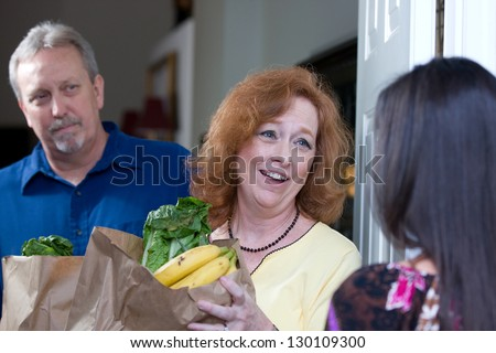 Woman delivers bags of food to the home of a down on their luck couple who have been laid off from their jobs. - stock photo