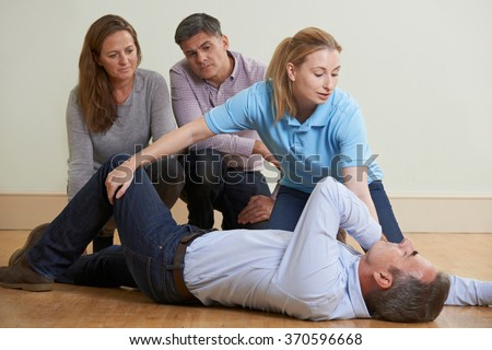 Woman Demonstrating Recovery Position In First Aid Training Class - stock photo