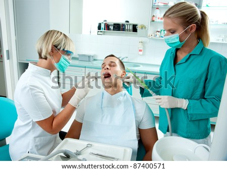 woman dentist and her assistant working on male patient - stock photo