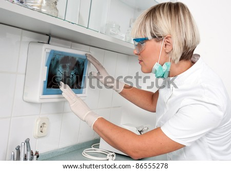 woman dentist looking at x-ray image - stock photo