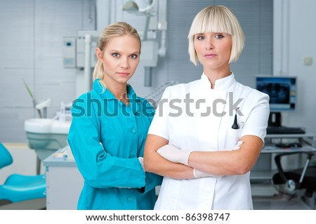 woman dentist standing in her office with her personal assistant - stock photo