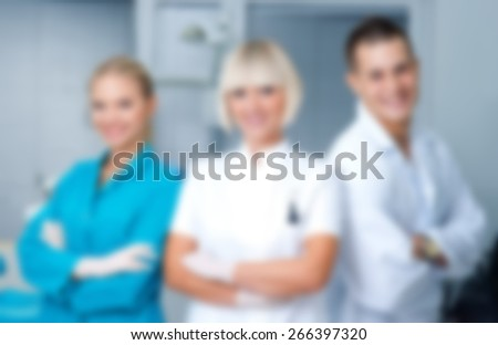 woman dentist standing in office with her personal assistants crew, blurred for presentation, abstract background - stock photo