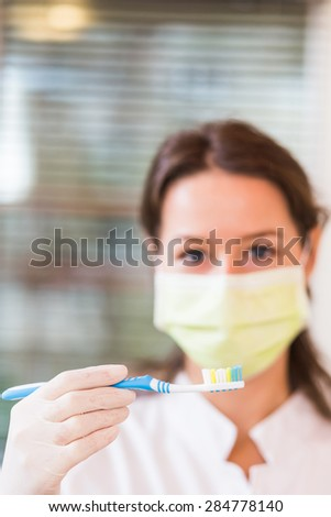 Woman dentist with mask, holding a toothbrush