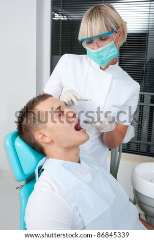 woman dentist working on patient teeth - stock photo