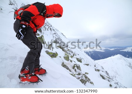Woman descending the mountain in bad weather during winter - stock photo
