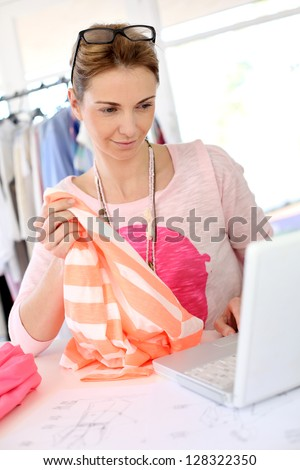 Woman designer in workshop looking at laptop - stock photo