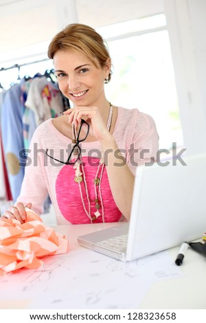 Woman designer in workshop looking at laptop