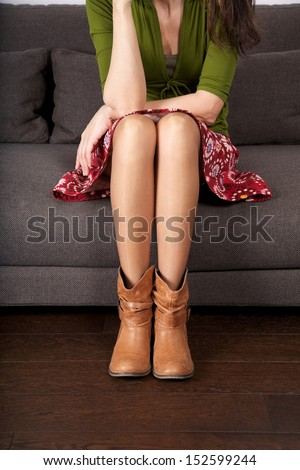 woman detail sitting on a brown sofa - stock photo