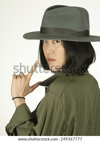 Woman detective looking over her shoulder wearing a hat