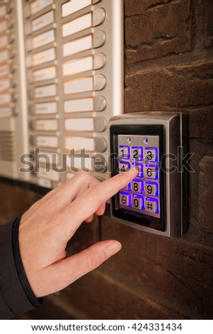 Woman dialing passcode on security keypad intercom to open entrance door of the apartment building. - stock photo