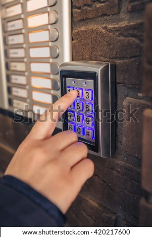 Woman dialing passcode on security keypad to open entrance door of the apartment building. - stock photo