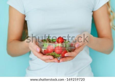 Woman diet concept portrait. Female model holding green salad - stock photo