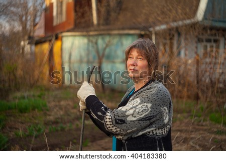 Woman digging the beds at the cottage and plants - stock photo