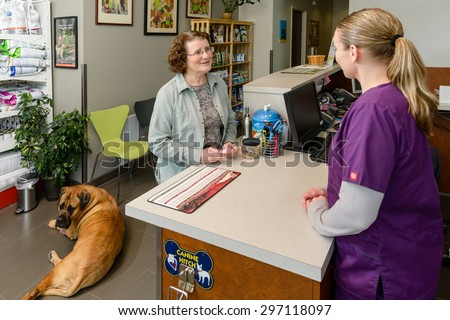Woman discuss her dog with vet assistant