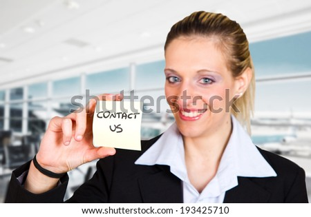 Woman displaying a contact us business card in the airport - stock photo