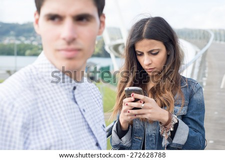 Woman distracted looking at her smart phone. The woman is not aware of her boyfriend. - stock photo