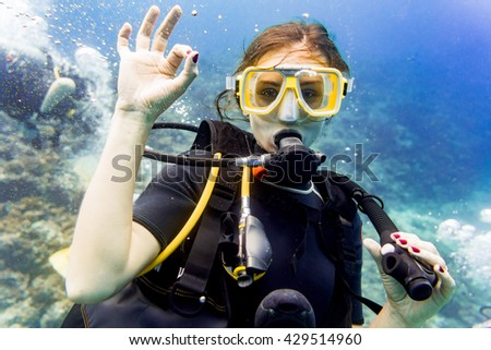 Woman diving in her vacation on coral reef giving the ok sign - stock photo