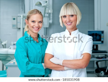 woman doctor gynecologist or oncologist with her assistant smiling in her office - stock photo