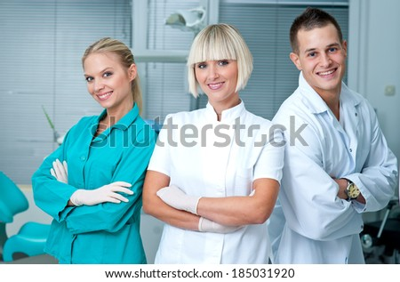 woman doctor gynecologist or oncologist with her assistants smiling in her office - stock photo
