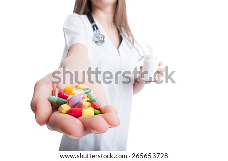 Woman doctor hand offering pills with focus on the multicolored capsules - stock photo