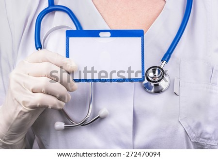 Woman doctor in a white coat holding a blank badge