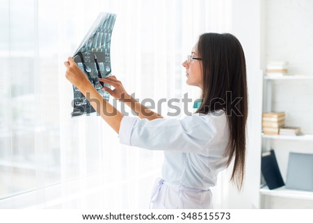 Woman doctor looking at the x-ray or MRI picture in hospital
