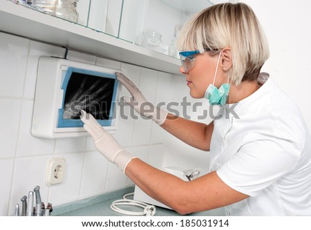 woman doctor looking at x-ray picture in her office - stock photo