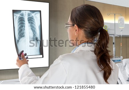 Woman Doctor Looking at X-Ray Radiography in patient's Room - stock photo