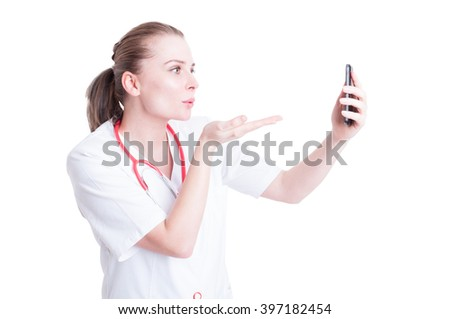 Woman doctor sending blowing kisses on video call as medical love concept - stock photo