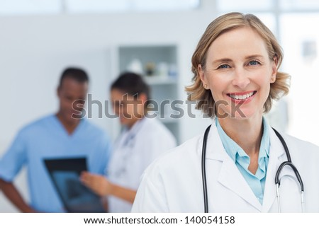 Woman doctor smiling and looking to the camera while a medical team is working - stock photo