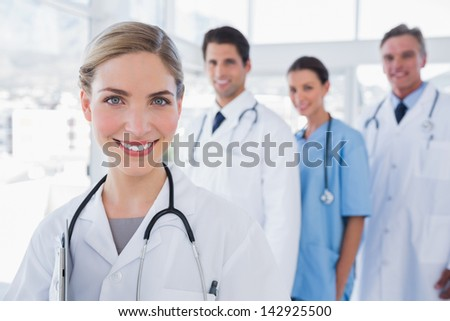 Woman doctor standing in front of her colleagues - stock photo