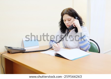 Woman doctor talking on the phone with the patient