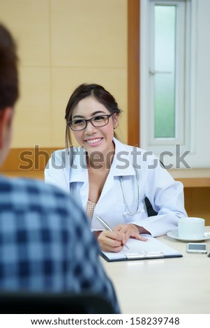 Woman doctor talking to her male patient at office, Mode is Thai ethnic. - stock photo