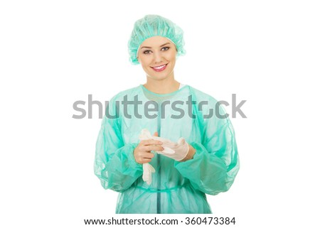 Woman doctor wearing medical gloves. - stock photo