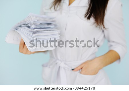 woman doctor with a bundle of sheets. - stock photo
