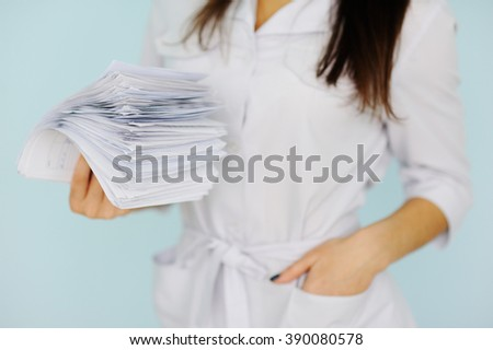 woman doctor with a bundle of sheets. Nurse with sick leave - stock photo