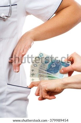 Woman doctor with stethoscope refusing bribes or kickbacks, polish currency money, patient giving money for medical services, concept of corruption - stock photo