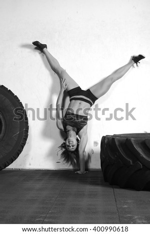 woman doing a handstand against a concrete wall - stock photo