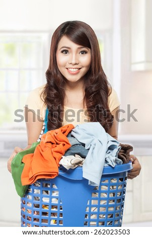 woman doing a housework holding laundry