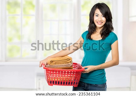woman doing a housework holding laundry in the house - stock photo