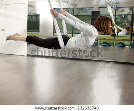 Woman doing anti gravity yoga exercise in fitness center. - stock photo