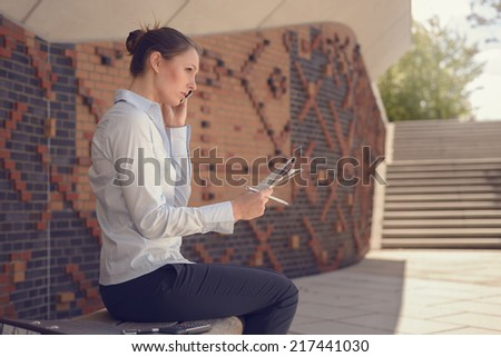Woman doing business in a commercial foyer sitting on a wall mounted bench against patterned brickwork talking on her mobile phone discussing her notes with a tablet alongside, conceptual of mobility