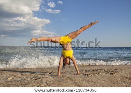 woman doing cartwheel on the beach fit female - stock photo