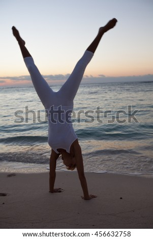 woman doing cartwheels on the beach at night