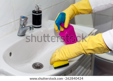 Woman doing chores in bathroom, cleaning sink and faucet with spray detergent. Cropped view - stock photo
