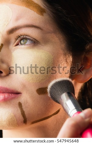 Woman doing contouring on her face in a studio