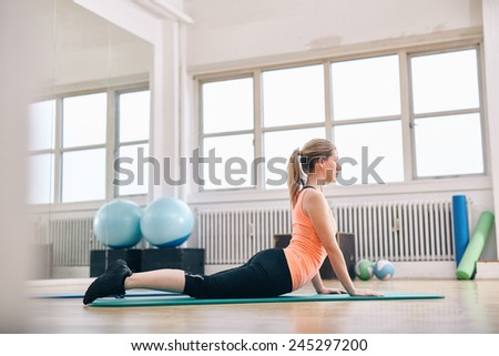 Woman doing core stretch on fitness mat. Attractive young woman doing yoga at gym. - stock photo