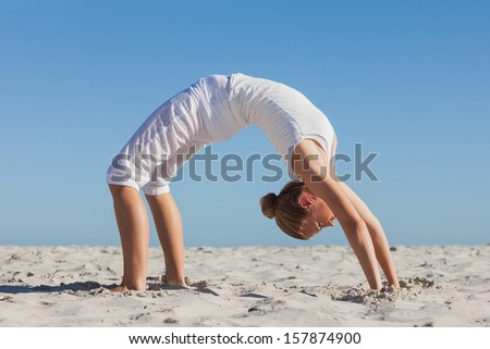 Woman doing crab yoga pose on the beach on a sunny day - stock photo